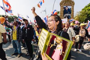 An Anti-Government protester carrying a portrait of the King and Queen of Thailand celebrating at a rally aimed at unseating the Prime Minister of Thailand. Anti-Government protesters led by the People's Democratic Reform Committee's (PDRC) marched towards Government House in Bangkok on Monday 9th December, 2013, where they heard the news that Prime Minister, Yingluck Shinawatra, brother of former