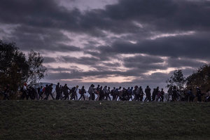 Migrants are escorted by Slovenian riot police to a registration camp outside Dobova, Slovenia, 23 October 2015.