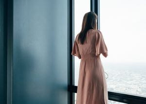 A young woman in pink dress at the window of the Willis Tower. Chicago, Illinois.