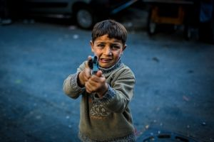 """A small kid is playing """"war-war"""" with a toy gun on the street. © Turjoy Chowdhury"""