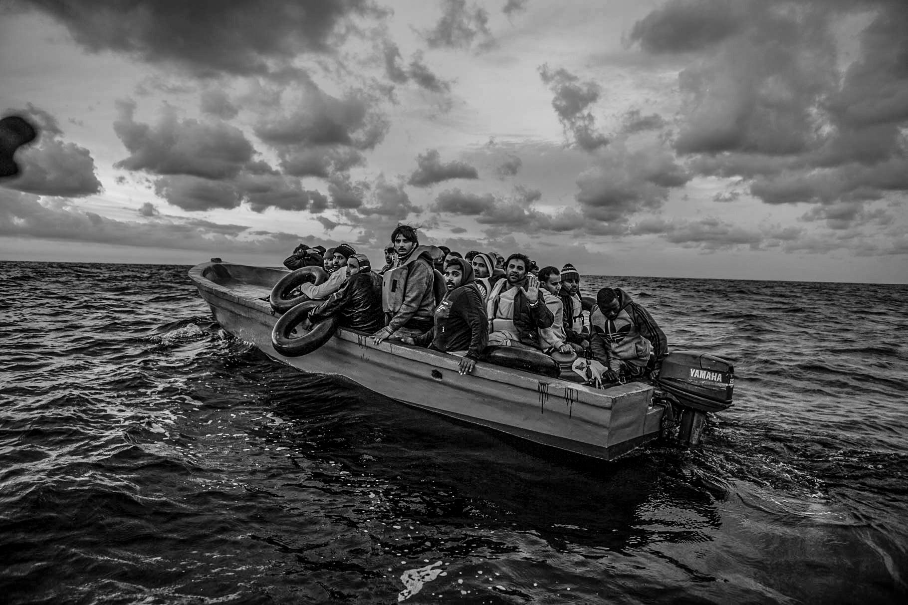 At dawn, a small wooden boat carrying 21 Bangladeshis and one Congolese is spotted drifting in international waters by Migrant Offshore Aid Station. The engine had broken down, and the migrants, who had set out before midnight from Libya, had been floating without direction or means of communication throughout the night. © Jason Florio/MOAS. Photojournalism Series Winner, Magnum Photography Awards 2017.