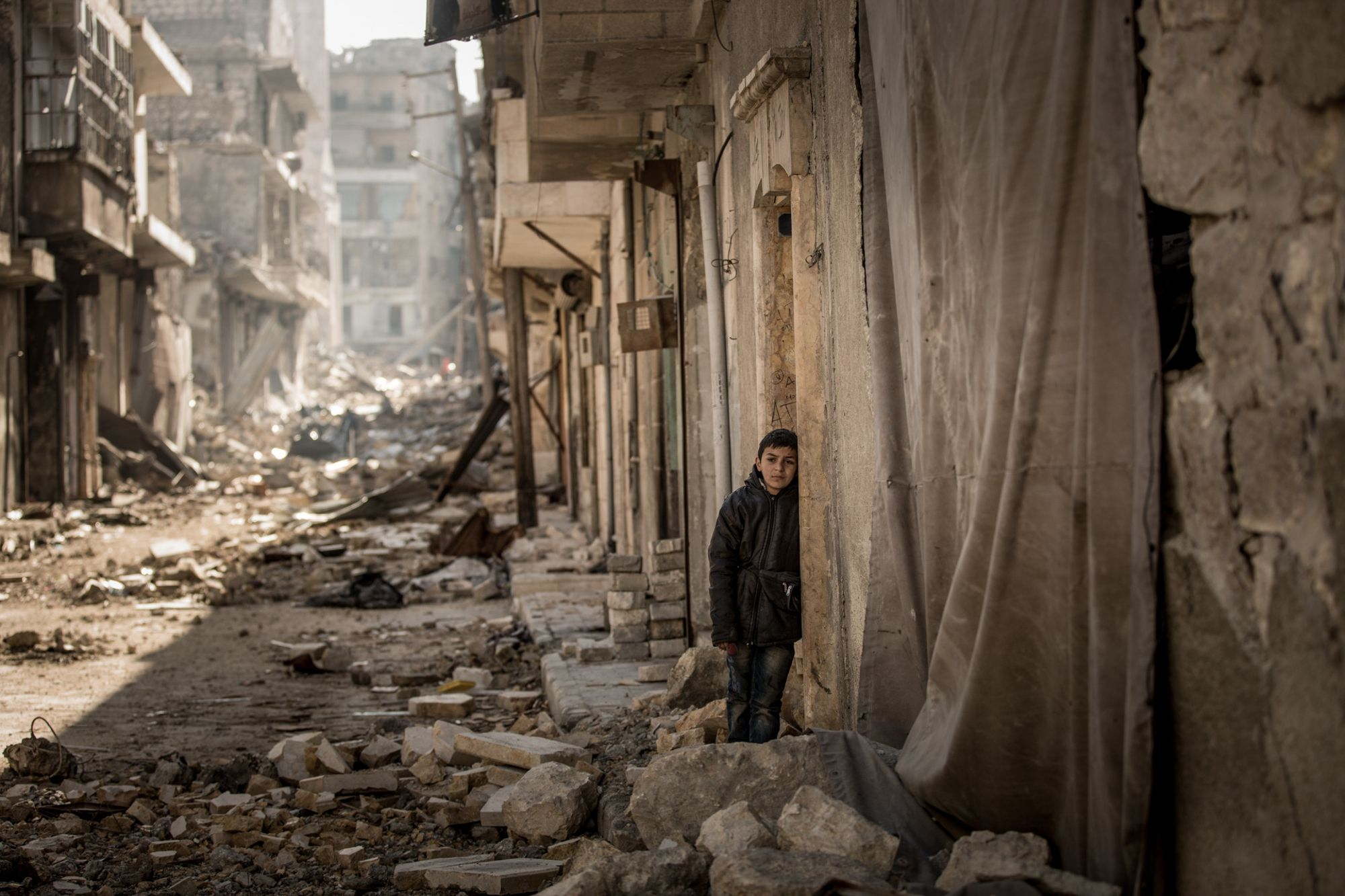 Syria, January 2017. A boy looks at the complete devastation outside of his own destroyed home. © Christian Werner/Zeitenspiegel. Juror's Pick, Magnum Photography Awards 2017.