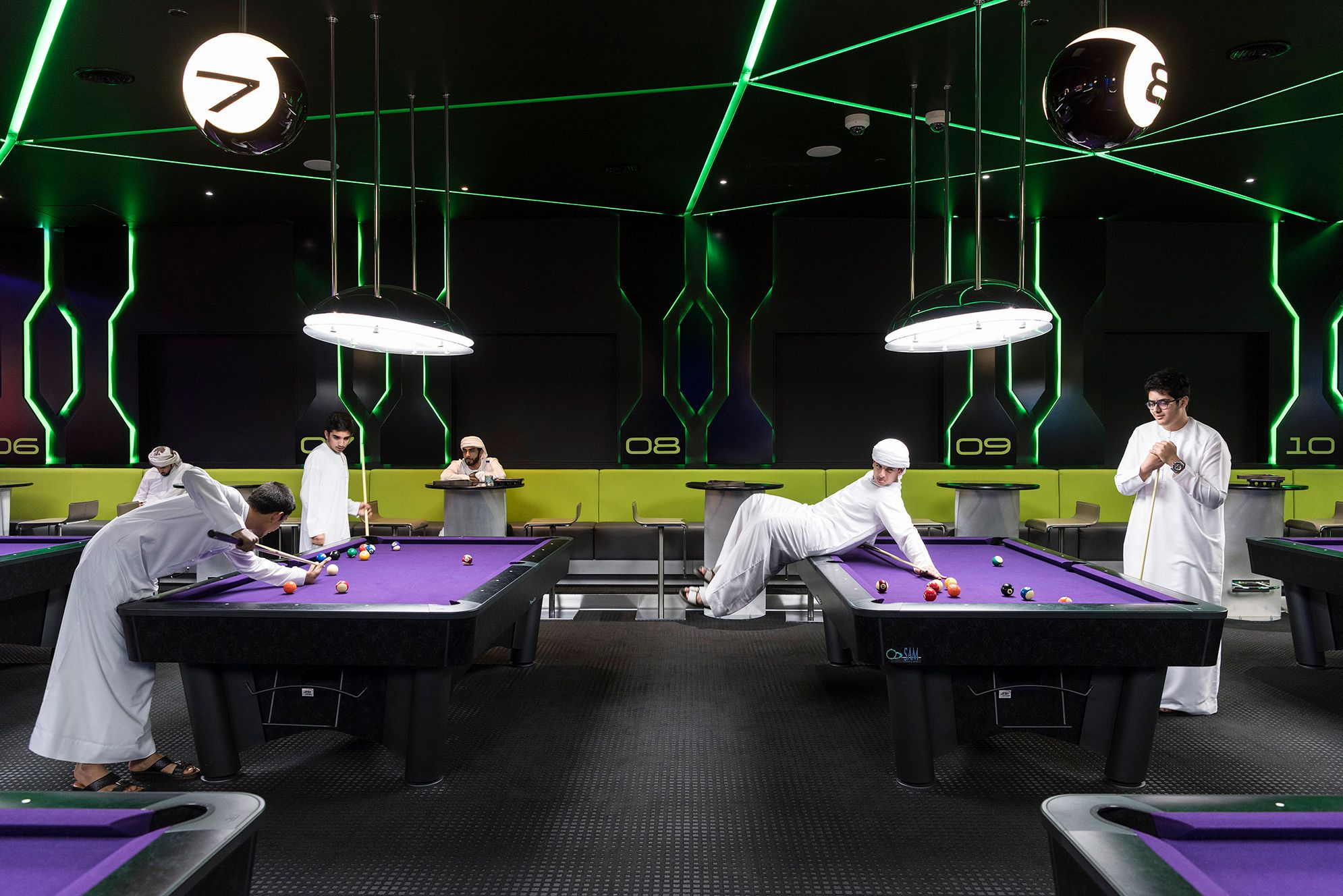 Hub Zero, Dubai, January 2017. Emirati boys playing a game of pool at Hub Zero, an immersive entertainment hub located at City Walk shopping mall. © Nick Hannes. Documentary Series Winner, Magnum Photography Awards 2017.